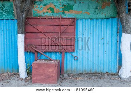 Wooden fire shield against the background of a blue wall