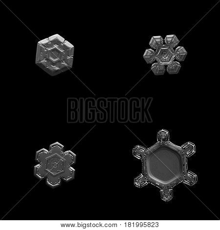 Set with four macro photos of real snowflakes: small snow crystals with simple shapes and beautiful inner patterns. Black and white version. Snowflakes isolated on black background.
