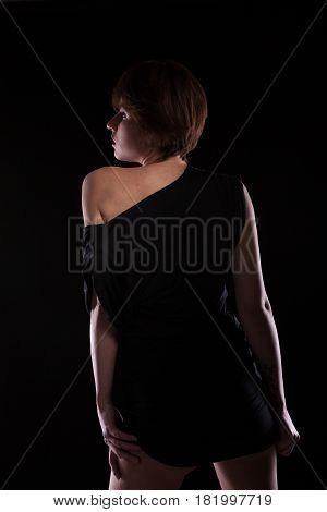 Sensual woman in black dress posing sexy on dark background in studio photo. Seduction and sensuality