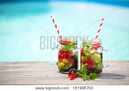 Glass of natural berry lemonade near pool