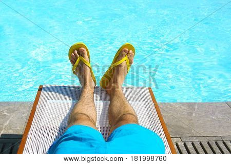 Young man lying on sunbed near pool. Summer vacation and travel concept