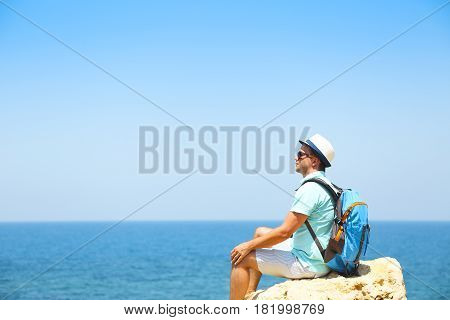 Man looking in to the horizon sitting on rock above the sea. Travel and summer vacation concept