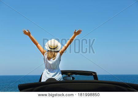 Happy young woman in car on the beach. Travel and summer vacation