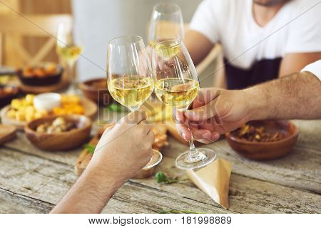 Hands with white wine glasses. Dinner and celebration