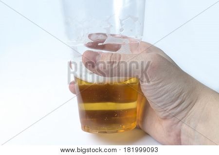 Hand holding glass with beer on white background.
