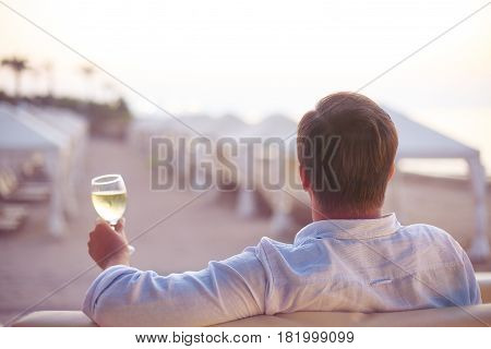 Relaxing man with glass of white wine on the beach