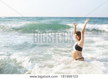 Happy pretty pregnant woman have fun and joy in the sea