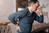 Close up side view of old man having terrible headache and sudden pain in back while standing at home. poster