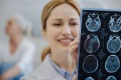Brain tomography. Selective focus if a MRI brain scan while being examined by a cheerful good looking delighted doctor poster