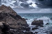 Foggy view of Pebble Beach California coast with storm clouds and rough seas causing waves to crash on rocks. The picture depicts the Pacific Ocean and tourism in Monterey America. The beach is shaped by erosion and climate change. poster