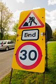 Temporary speed restriction end of road works sign showing 30 miles per hour limit used in the United Kingdom with defocussed traffic in the background poster