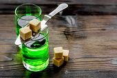 green absinthe in glass with cubes of sugar on wooden table background poster