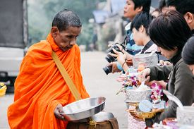 Kanchanaburi, Thailand - December 09, 2013: Buddhist giving alms with foods and flowers to a Buddhist Monk at Sangkhlaburi's Mon Village in the morning