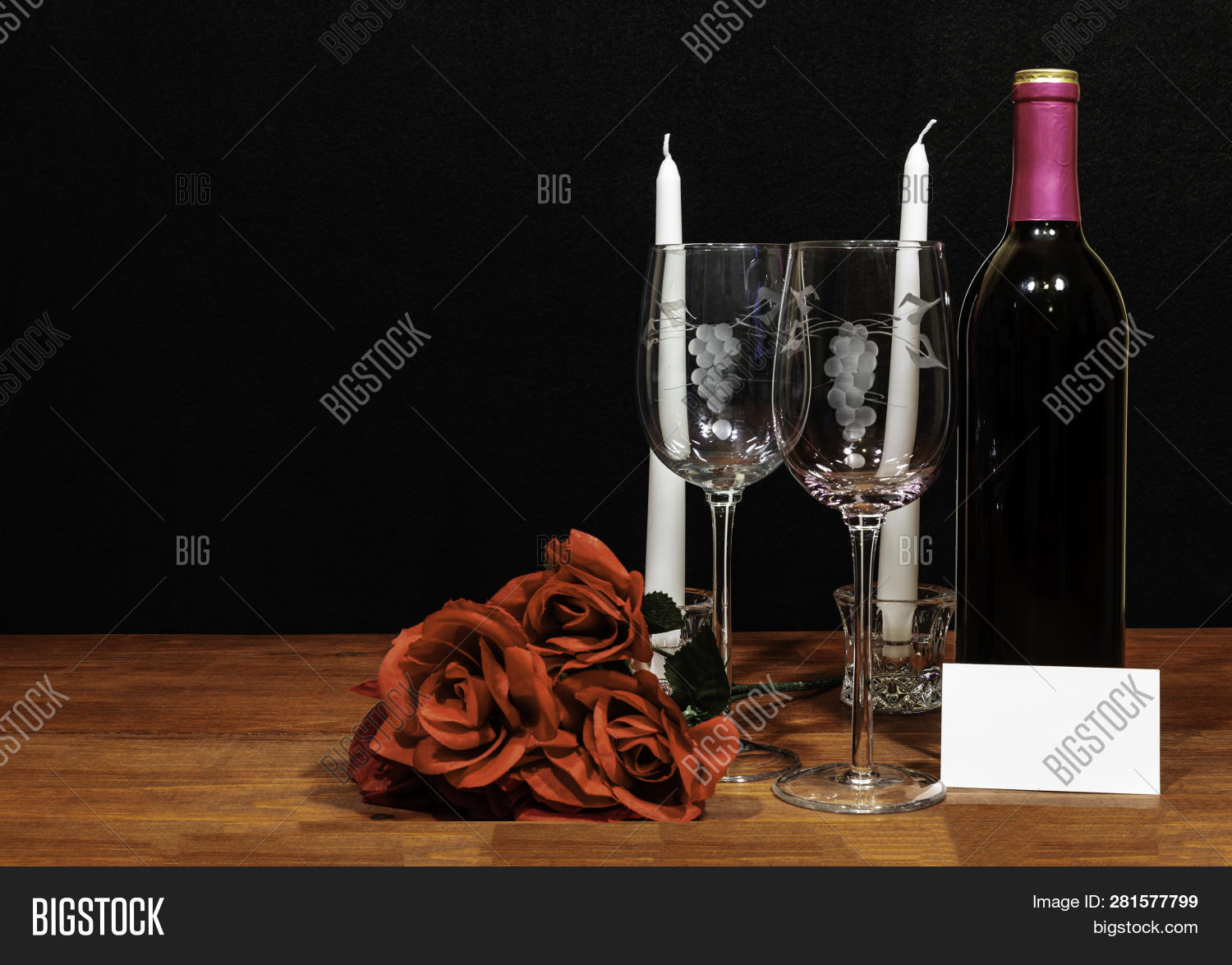 3a8a1c1b61bd Beautiful etched wine glasses and bottle of red wine, white candles and  bouquet of red roses on wooden table with card on dark background.