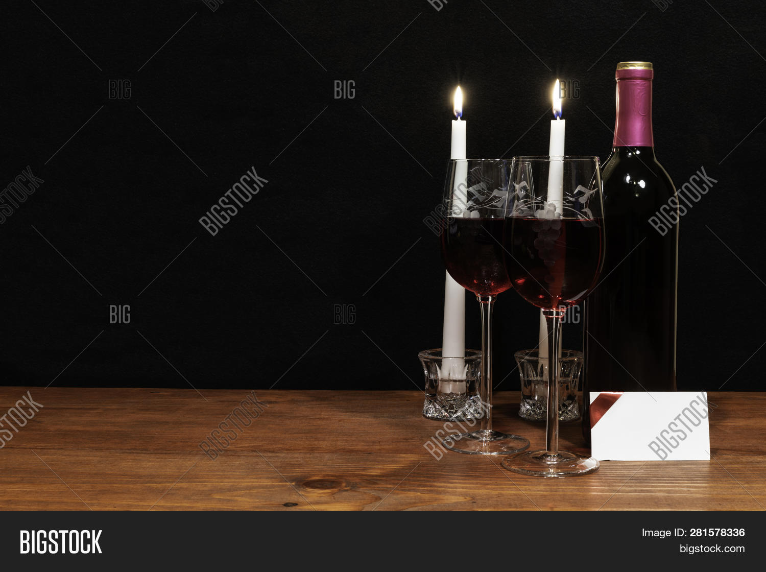 0876a7ae1828 Beautiful etched wine glasses and bottle of red wine, white candles, on  wooden table with card on dark background. Valentines, Mothers Day, Easter,  ...