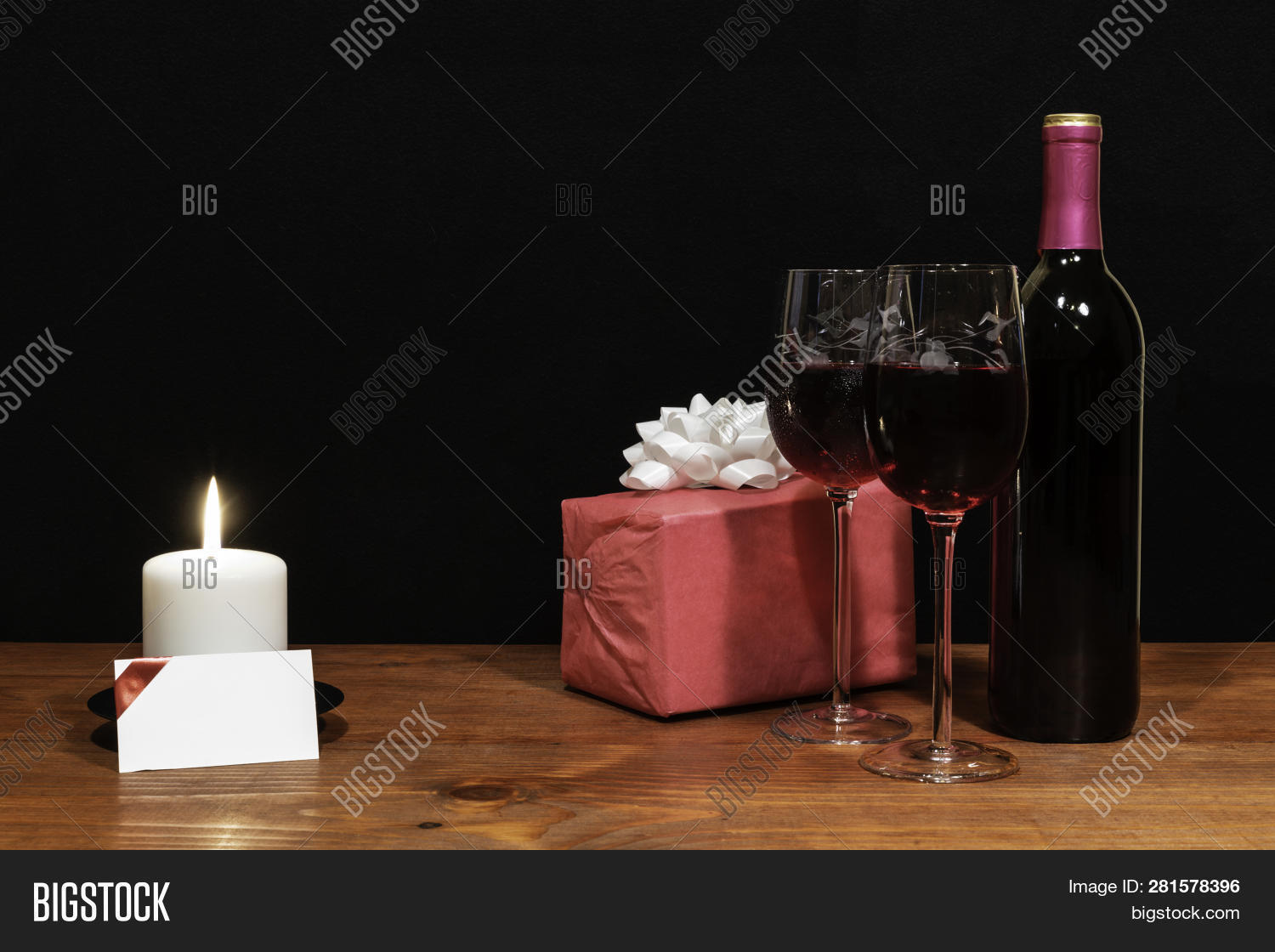 22d81186cd86 Beautiful etched wine glasses and bottle of red wine, white candle, wrapped  present with bow on wooden table with card on dark background.