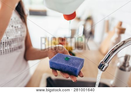 Woman putting cleanser to a sponge to wash pan in the kitchen-sink. Hand washing dishes. Close-up. poster