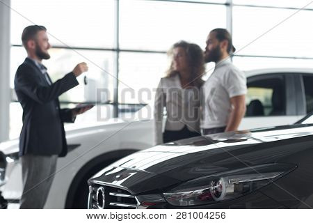 Black Car Hood Close Up. Manager Standing Opposite Customers Of Car Dealership. Car Dealer Holding C