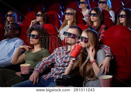 Side View Of Cute Couple Having Date And Watching Movie In 3d At Cinema. Young Girl And Man Sitting