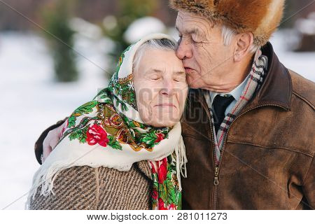 Portrait Of Senior Couple. Elderly Man Kiss His Wife In Weighty. Old Couple Walkink In The Park In W