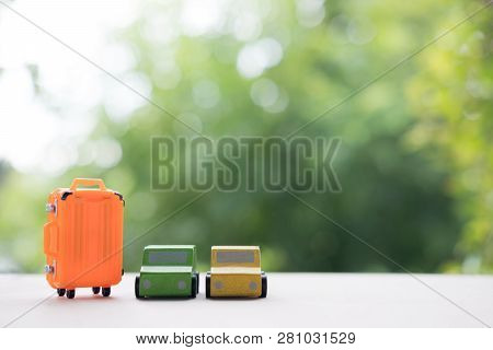 Miniature Toy Car And Miniature Orange Suitcases On Nature Background. Concept Of Travel Or Travel I