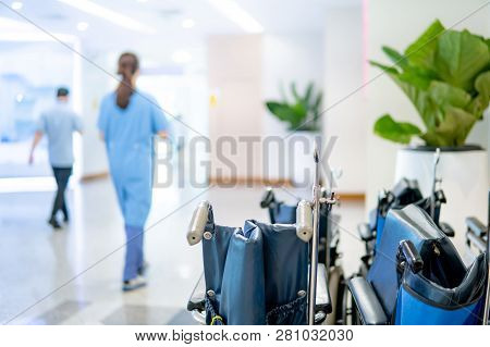 Group Of Blue Folding Wheelchair With Blured Doctor And Nurse Walking Through The Corridor In Hospit