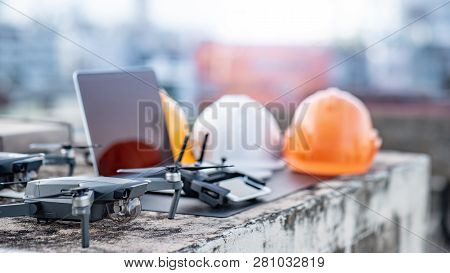 Drone, Remote Control, Laptop Computer, Smartphone And Protective Helmet At Construction Site. Using