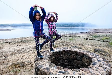 Twin Girls Standing On Remains Of Ancient Roman Water Well.