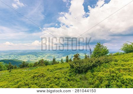 View In To The Valley From Grassy Hill. Beautiful Summer Scenery In Mountains. Dynamic Cloudscape On