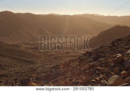 Valley with small village between high mountains. View from Mount Sinai (Mount Horeb, Gabal Musa). Scenic winter morning. Sinai Peninsula of Egypt. poster