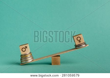 Gender Pay Gap. Wooden Cubes With Male And Female Gender Signs On Seesaw With Different Stacks Of Co