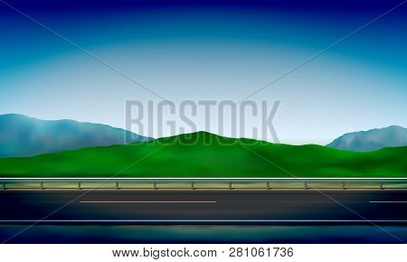 Side View Of A Road With A Crash Barrier, Roadside, Green Meadow In The Hills And Clear Blue Sky Bac