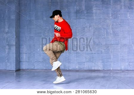Talented Young Rapper In Movement. Fashion Style Young Boy Dancing Rap On Beton Wall Background. Hip