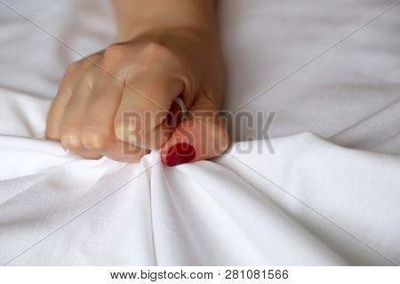 Female hand with red nails pulling and gripping white bedsheet in ecstasy. Orgasm of woman on the bed, having sex, feelings and emotion poster