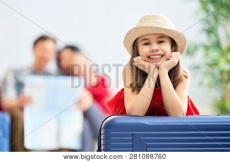 Go on an adventure! Happy family preparing for the journey. Mom, dad and daughters are packing suitcases for the trip.
