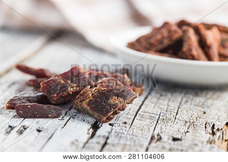Beef jerky pieces on old wooden table.Marinated dried meat.