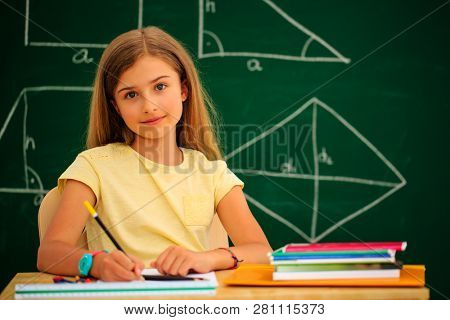 Back to school.. Funny beatifull girl sitting in the clasroom against blacboard. Child in school with book and accessories. Education concept