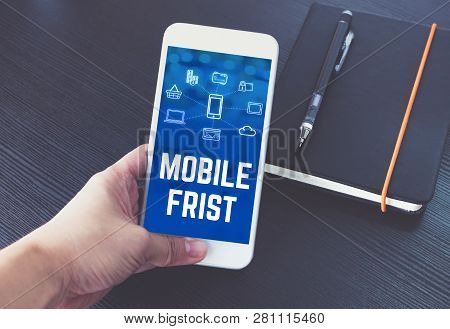 Hand Holding Mobile Phone With Mobile First Word And Feature Icon Over Notebook On Black Wood Table