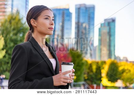 Asian business woman driking coffee cup outside on break from office pensive contemplative looking away at city background outdoor. Businesswoman lifestyle.