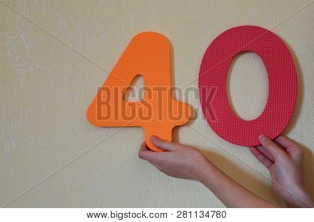 40 - Hands Holding Colorful Number Four And Zero Or Forty On Mild Yellow Wall Background With Copy S