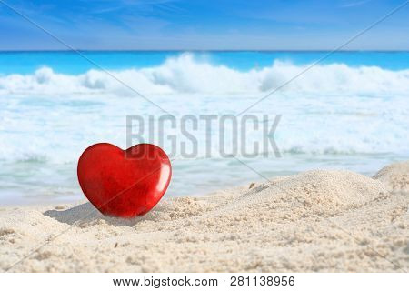 Beautiful red Valentines day heart on a tropical white sand beach with ocean waves and a bright blue sky in the background. Valentine love or beach wedding concept.