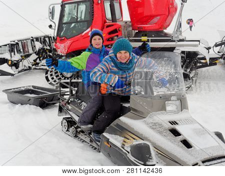 Lead Sit On A Snowmobile On A Snow Slope.