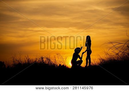 Silhouette Of Couple Of Loves Behind The Sunset,man Propose Marriage To Girlfriend,he Kissed Her Han