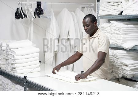 An African Male Hotel Worker Folds A Clean White Towel. Hotel Staff Workers. Hotel Linen Cleaning Se