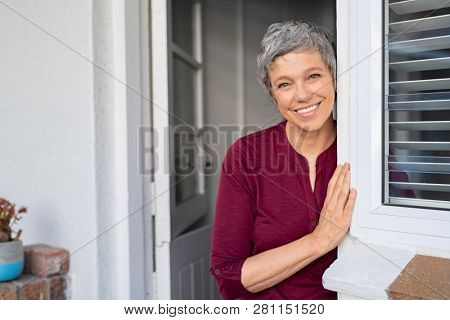 Portrait of senior woman standing while leaning against door at home and looking at camera. Smiling mature woman standing at doorway. Portrait of old lady with toothy smile standing at home entrance.