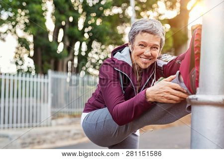 Smiling retired woman listening to music while stretching legs outdoors. Senior woman enjoying daily routine warming up before running. Sporty lady doing leg stretches and looking at camera.