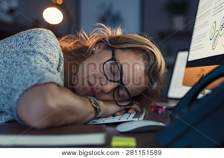 Mature business woman wearing eyeglasses and sleeping on computer keyboard in office. Closeup face of tired businesswoman doing overtime sleeping . Overwork and procrastination concept. Sleepy woman.