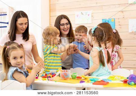 Kindergartener With Kids Group After Lesson In Classroom