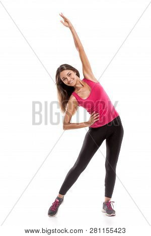 Studio Shot Of Fitness Woman Doing Stretching Workout. Full Length Shot Of Young Woman Wearing Pink