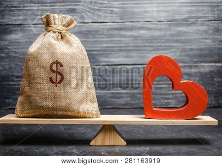 Bag With Money And Red Wooden Heart On The Scales. Money Versus Love Concept. Passion Versus Profit.